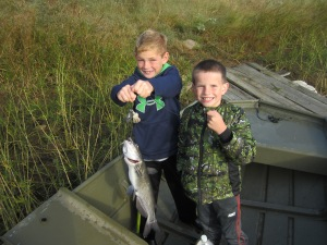 Elij and Landon displaying their catch from a jug-line.